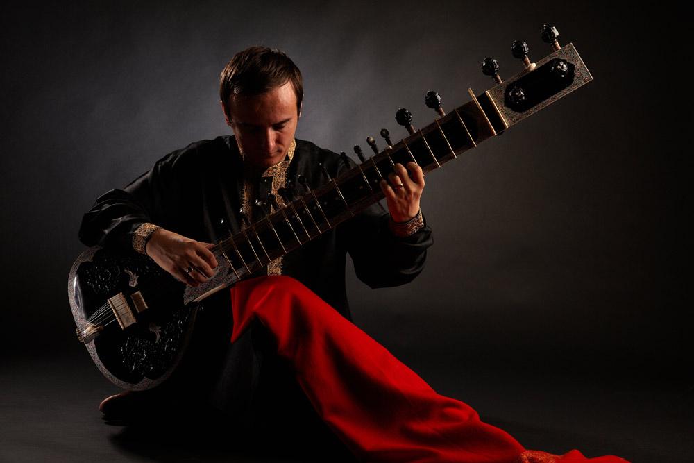sitar tinut de instrumentist in pozitia clasica de cantat