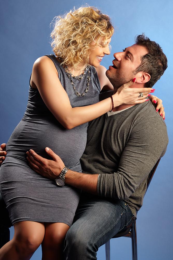 cuplu fericit barbatul tine gravida pe genunchi