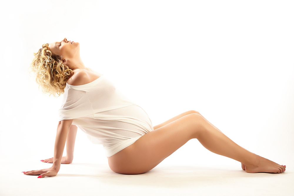 femeie gravida seminud asezata pe jos
