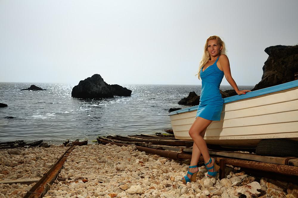 Fotomodel pe plaja langa barca